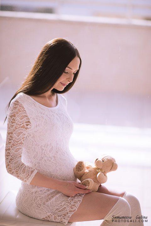 אישה בהריון יושבת עם דובי