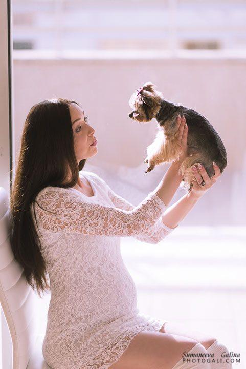 אישה בהריון בביתה יושבת עם כלבה