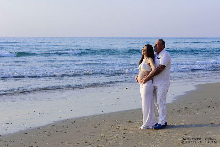 הורים לעתיד מתחבקים בחוף ים