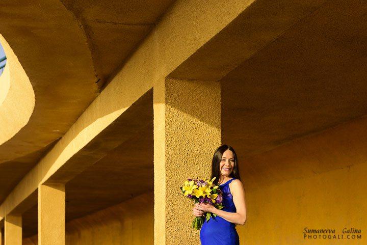 צילום של אישה בהריון עם פרחים בתוך מבנה